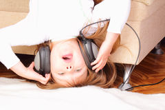 Beautiful little girl upside down with headphones Stock Photos