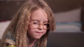 Beautiful little girl using computer in bedroom stock video