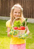 Beautiful little girl with vegetables in basket Royalty Free Stock Photos