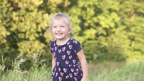 Beautiful little girl walks in a field at sunset stock footage