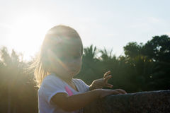 Beautiful little girl washing her hands in the fountain.On the Sunset. serious thoughtful face. Royalty Free Stock Photography