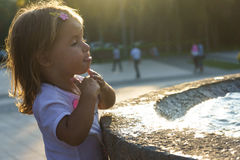 Beautiful little girl washing her hands in the fountain.On the Sunset. serious thoughtful face. Royalty Free Stock Photo