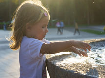 Beautiful little girl washing her hands in the fountain.On the Sunset. serious thoughtful face. Stock Images