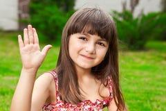 Beautiful little girl waves her hand stock image