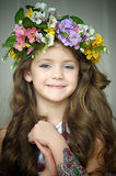 Beautiful little girl wearing a wreath of flowers. And a bracelet on her arm, studio photo royalty free stock photography
