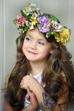 Beautiful little girl wearing a wreath of flowers. And a bracelet on her arm, studio photo stock photography