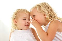 Beautiful little girl whispering to her sister. Close up portrait of beautiful little girl whispering to her sister royalty free stock image
