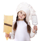 Beautiful little girl in a white apron and holding a wooden grat Royalty Free Stock Images