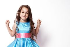 Beautiful little girl. White background. Blue dress. Brown hair. Happy smile Stock Photos