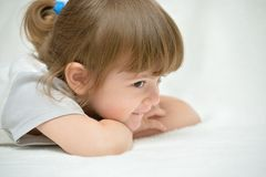 Beautiful little girl on a white blanket Stock Images