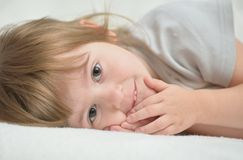 Beautiful little girl on a white blanket Royalty Free Stock Photography