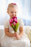 Beautiful little girl in a white dress with a bouquet of pink tu Stock Photo