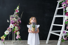 The beautiful little girl in a white dress with a flower makes a wish at the birthday Stock Images