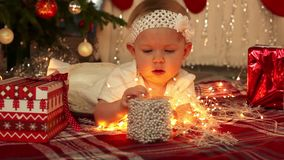 Beautiful little girl in white dress lies on the floor at festive Christmas tree and a lot of presents. 1920x1080. Beautiful little girl lies on the floor at stock footage