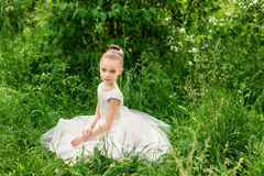 Beautiful little girl in a white dress posing in the grass Royalty Free Stock Images