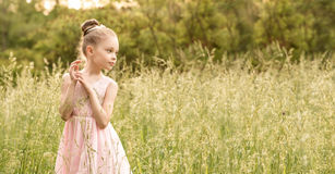 Beautiful little girl in a white dress posing in the grass Royalty Free Stock Image