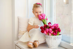Beautiful little girl in a white dress sitting on a windowsill w Royalty Free Stock Image