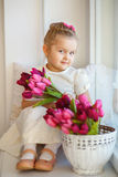 Beautiful little girl in a white dress sitting on a windowsill w Royalty Free Stock Images