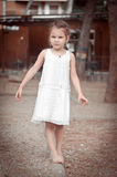 Beautiful little girl in a white dress walking barefoot on a log Royalty Free Stock Photos
