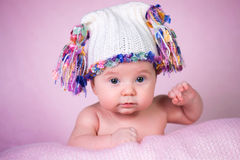 Beautiful little girl in white knitted cap on a pink background. Beautiful little girl in a white knitted cap on a pink background Stock Photo