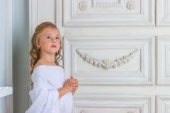 Beautiful little girl in white robe praying Stock Photo