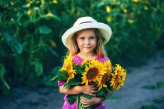 Beautiful little girl in white wide brimmed hat with sunflower flowers in the field Stock Photos