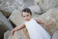 Beautiful little girl who takes pictures on the rocks Royalty Free Stock Photo