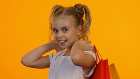 Beautiful little girl winking at camera and showing red shopping bags, discounts stock footage