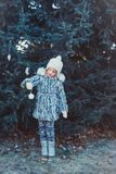 The beautiful little girl in winter wood. The girl is dressed in a gray fur coat. She is holding a white Christmas ball stock photo