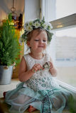 Beautiful little girl in a wreath on the head in green and white. Party dress,  Princess. Royalty Free Stock Image