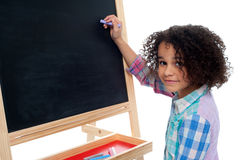 Beautiful little girl writing on classroom board Stock Photos