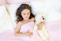 Beautiful little girl 5-6 years old sleeping in a bed with a Teddy bear