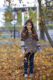 Beautiful little girl with yellow leaves in autumn park Stock Images