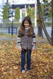 Beautiful little girl with yellow leaves in autumn park Royalty Free Stock Photo