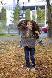 Beautiful little girl with yellow leaves in autumn park Royalty Free Stock Images