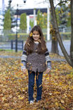 Beautiful little girl with yellow leaves in autumn park Stock Photos