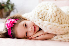 Beautiful little girle laying under the white knitted blanked, s. Beautiful little girl laying under the white knitted blanked, smiling and preparing to sleep Royalty Free Stock Photography