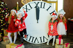 Beautiful little girls with a big clock Stock Images