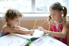 Beautiful little girls, homework at home royalty free stock photography