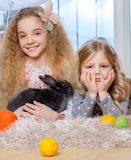 Beautiful little girls lying on carpet and playing with bunny. Stock Images