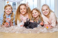 Beautiful little girls lying on carpet and playing with cute bunny. Stock Image