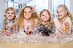 Beautiful little girls lying on carpet and playing with cute bunny. Royalty Free Stock Image