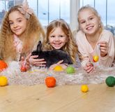 Beautiful little girls lying on carpet and playing with cute bunny. Royalty Free Stock Photos