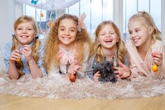 Beautiful little girls lying on carpet and playing with cute bunny. Stock Photos