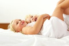 Beautiful little girls lying together on bed Stock Photo
