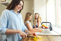 Beautiful little girls with they mother in the kitchen preparing stock images