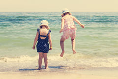 Beautiful little girls (sisters) are running and playing on the Stock Photos