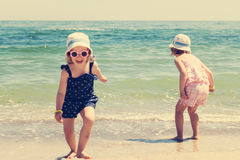 Beautiful little girls (sisters) are running and playing on the Stock Image