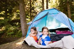 Beautiful little girls in tent camping in the forest. Stock Photo