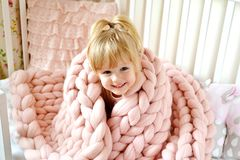 Little Girl Sitting on Bed with a Knitted Giant Plaid. Beautiful Little Happy Blond Ginger Girl Sitting on Bed with a Pink Knitted Giant Plaid stock photos